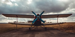 Front view to biplane standing on airports with cloud sky