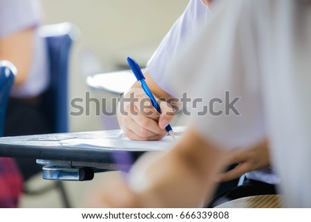 front view.university or high school student holding pencil.sitting on row chair writing final exam in examination room or study in classroom.student in uniform.space for text.education concept