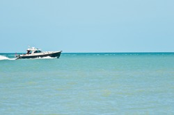 front view, very far away of a power yacht crossing the tropical waters of the gulf of Mexico on a winer, sunny day