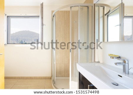 Front view with sink with shower and open window on the Swiss hills, in ticino. Nobody inside