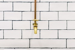 front view with space for text, Retro golden water tap with copper pipes on wall with white tiles