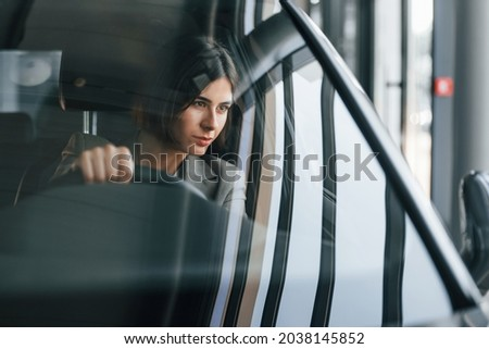 Front view. Woman testing new car. Sitting indoors in modern automobile.