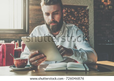 Front view.Young bearded businessman sits in cafe at table,uses digital tablet.On desk is notebook,cup of coffee.Man working,studying.Online education,marketing.E-learning,e-commerce. Instagram filter #726046876