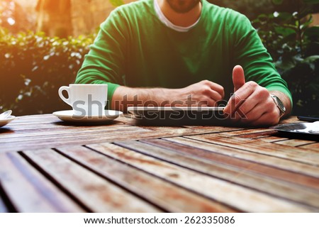Front view young man sitting at the table with cup of coffee, digital tablet and smart phone, man\'s hands typing message on touch screen tablet while sitting on balcony terrace with plants, flare