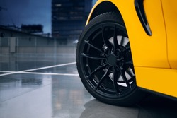 Front wheel and rims of modern sport car. Car reflection in a wet concrete floor of parking