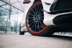 Front wheel of modern sportcat. Black rims on the white supercar
