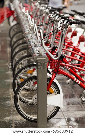 Front wheels of red bikes standing in a row at bicycle-sharing system #695680912
