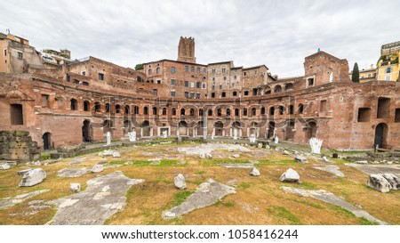 Front wide angle view of the Trajan's Market ruins in Rome city centre, Italy, with dramatic cloudy sky in the background. #1058416244