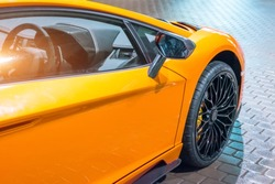 Front wing and the wheel of the car are a supercar, at night in a parking lot in the city.