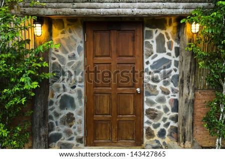 Front wooden door of residence, surrounded by nature in evening