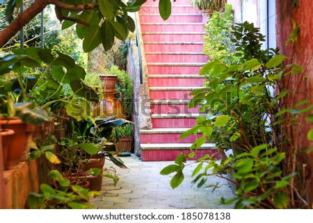 Front yard of the building in Anacapri island, Italy. Intimate garden with pink staircase and some old jars.