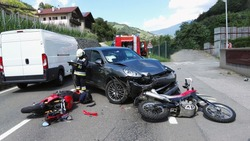 Frontal car accident with two motorbikes and car. Massive motorcycles crash collision hit by car following a risky road overtaking. Firefighter performs accident reconstruction of an multiple crash.