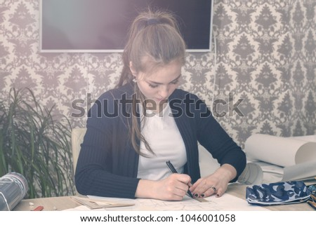 Frontal portrait of a young female student is engaged at the table draws sketches, sketches, plans, architecture. training and practice. #1046001058