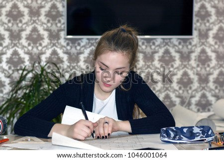 Frontal portrait of a young female student is engaged at the table draws sketches, sketches, plans, architecture. training and practice. #1046001064
