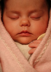 frontal portrait of an adorable sleeping newborn baby girl wrapped in a pink blanket