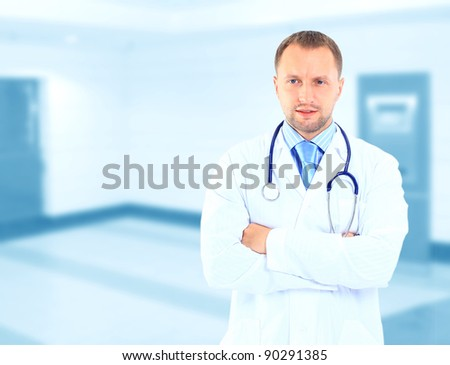 Frontal portrait of doctor in white coat and stethoscope with arms crossed - stock photo
