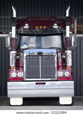 Frontal view of a large red big rig truck parked at the depot