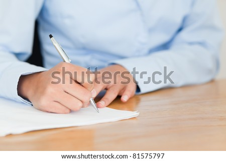 Frontal view of a young woman writing on a sheet of paper while sitting at the office