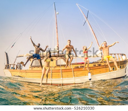 Frontal view of young multiracial friends jumping from wooden sailing boat on sea trip - Rich happy guys and girls having fun in summer party day - Exclusive vacation concept - Warm vintage filter