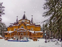 Frontal view Patrimony of Russian Father Frost among fir trees and white snowy field in Veliky Ustyug. Winter fairy-tale wooden palace in the forest among and snowflakes on daylight, cloudy sky.