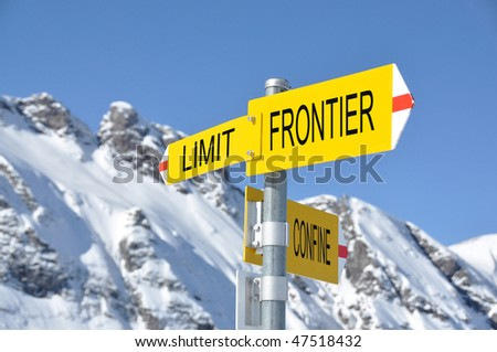 FRONTIER-LIMIT-CONFINE sign against mountain scenery