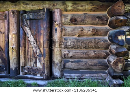 Frontier log cabin.  Front door and wall of log cabin built within the walls of a fort built on the frontier of South Dakota.