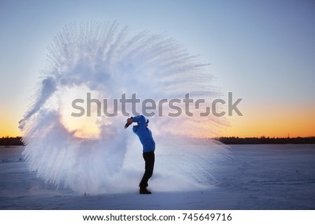 frost effect hot water freezes man pours boiling water #745649716