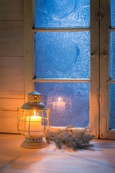 Frosted blue window and burning candle for Christmas