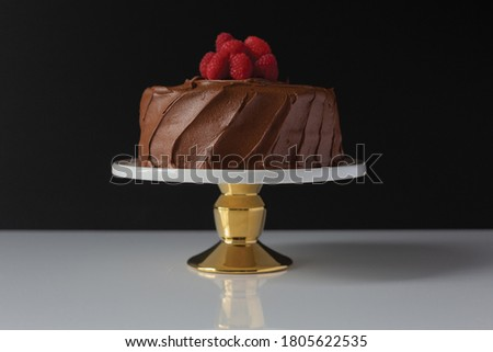 Frosted chocolate cake with raspberries on a gold cake stand with a black background and white countertop.   Foto stock ©