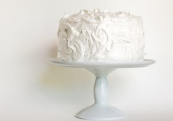 frosted white cake on stand