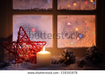 Frosted window with festive candles and holiday decorations
