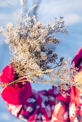 Frosty branch in the hand of a child in bright winter clothes on a blue background close-up. Winter bouquet. Gift for mom. Winter sunny frosty day. Vertical shot, selective focus.
