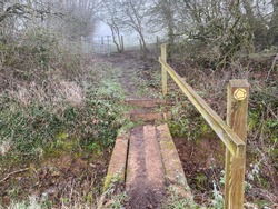 Frosty countryside scene of a footpath with a wooden bridge crossing a muddy ditch. A post with a directional arrow showing the way to another kissing gate beyond.