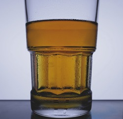 Frosty glass of beer on white back-lit background, lager beer, wet glass, cold alcohol drinks. Closeup cold glass of beer on white background. Refreshment concept. Cool alcohol drinks.