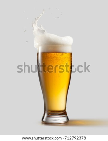 Frosty glass of light beer with foam