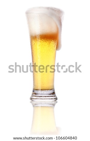 Frosty glass of light beer with foam isolated on a white background
