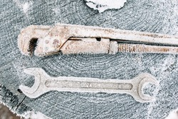 Frosty mechanical instruments on old wooden stump. Left outside tools in winter. Cold, early frosts, hoar, yard concept