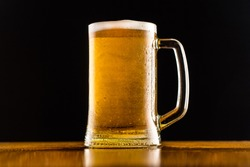 Frosty mug of beer close up on wooden table against black background.