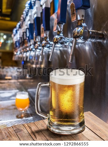 Frosty mug of light beer on the old wooden table. Pub interior and bar counter with beer taps at the background.