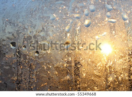 frosty natural pattern and sun on winter glass