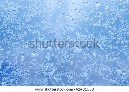 Frosty natural pattern on winter glass with drops