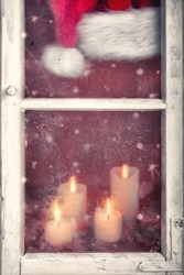 frosty window at christmas time with candles and red santa claus hat