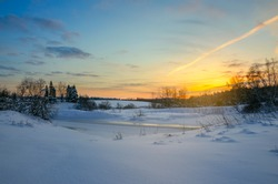 Frosty winter landscape with frozen ice bound river.Twilight.Cold morning.Snow covered trees.Sunrise.Moscow region,Russia.