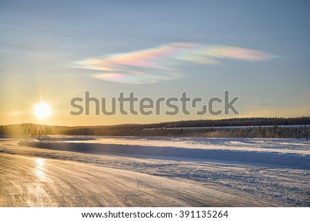 Frosty winter sunset in Ivalo, Lapland. Iced lake with a handling track, snow on a side. Ice crystal weird halo in the blue sky.