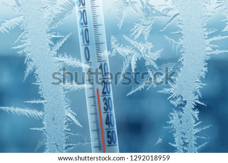 Frosty winter window with ice patterns and a thermometer showing a minus temperature. #1292018959