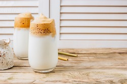 Frothy Dalgona Coffee, a trendy fluffy creamy whipped coffee. Korean drink: coffee foam made of instant coffee, sugar and water with milk. New popular food and drink trend. Bamoo straw and milk jug