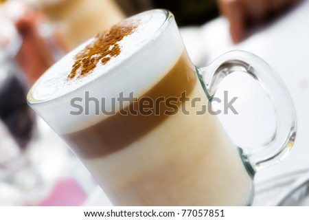 Frothy, layered cappuccino in a clear glass mug with cinnamon sprinkled on top
