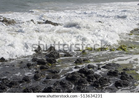 Frothy white  Indian Ocean waves breaking onto the  dark basalt rocks and sandy shore   at  Ocean Beach Bunbury Western Australia on a  sunny late morning  in winter  are delicate and foamy. #513634231