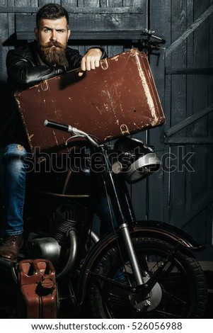 Frown bearded man hipster biker brutal male with beard and moustache in leather jacket sits on motorcycle with vintage suitcase and gas can on wooden background #526056988