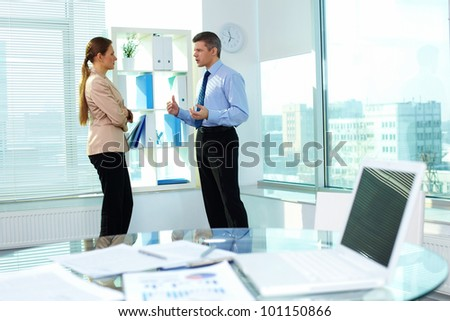 Frowning businessman explaining something to his female colleague